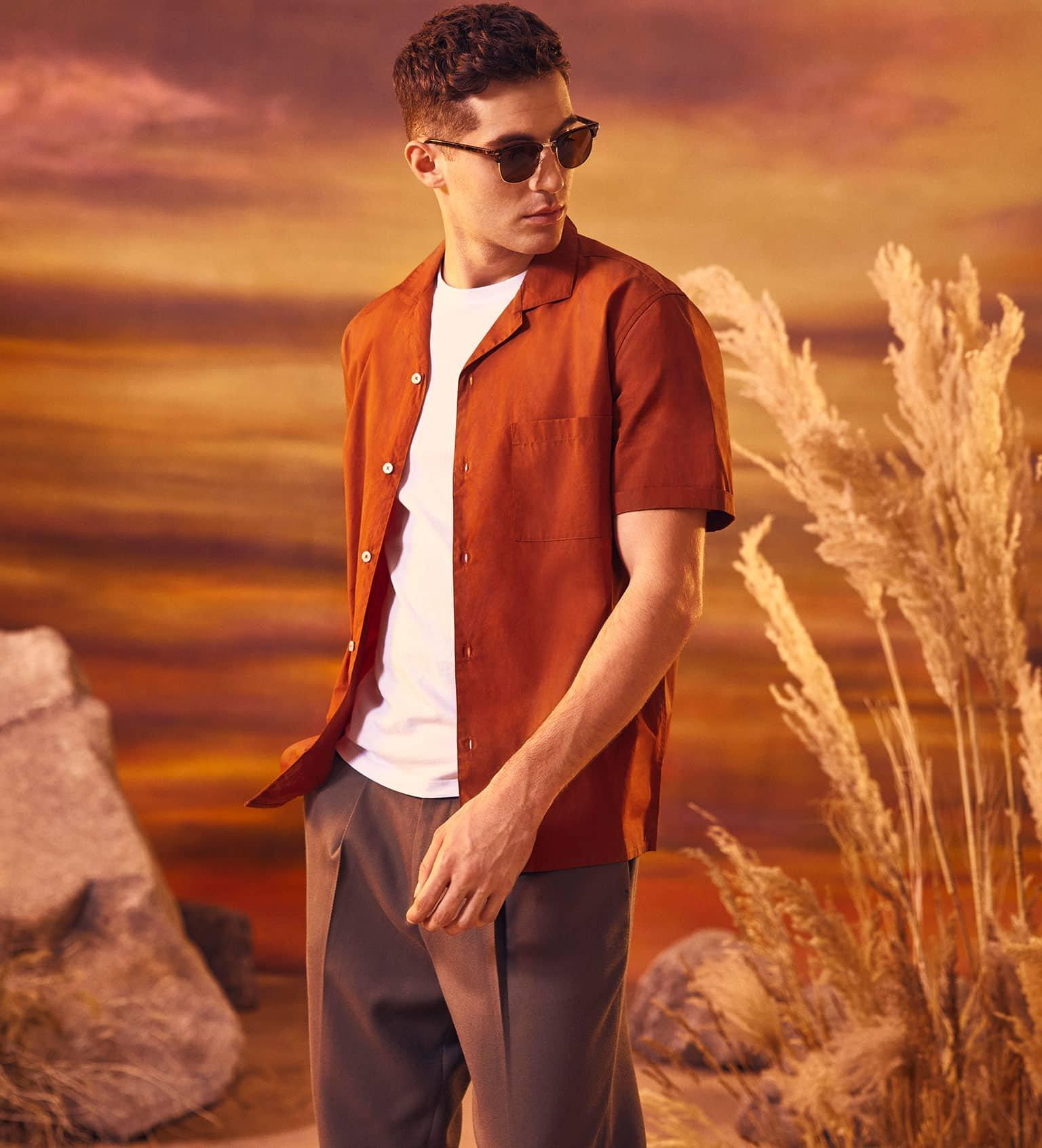 Model wears orange shirt over white t-shirt with brown trousers.