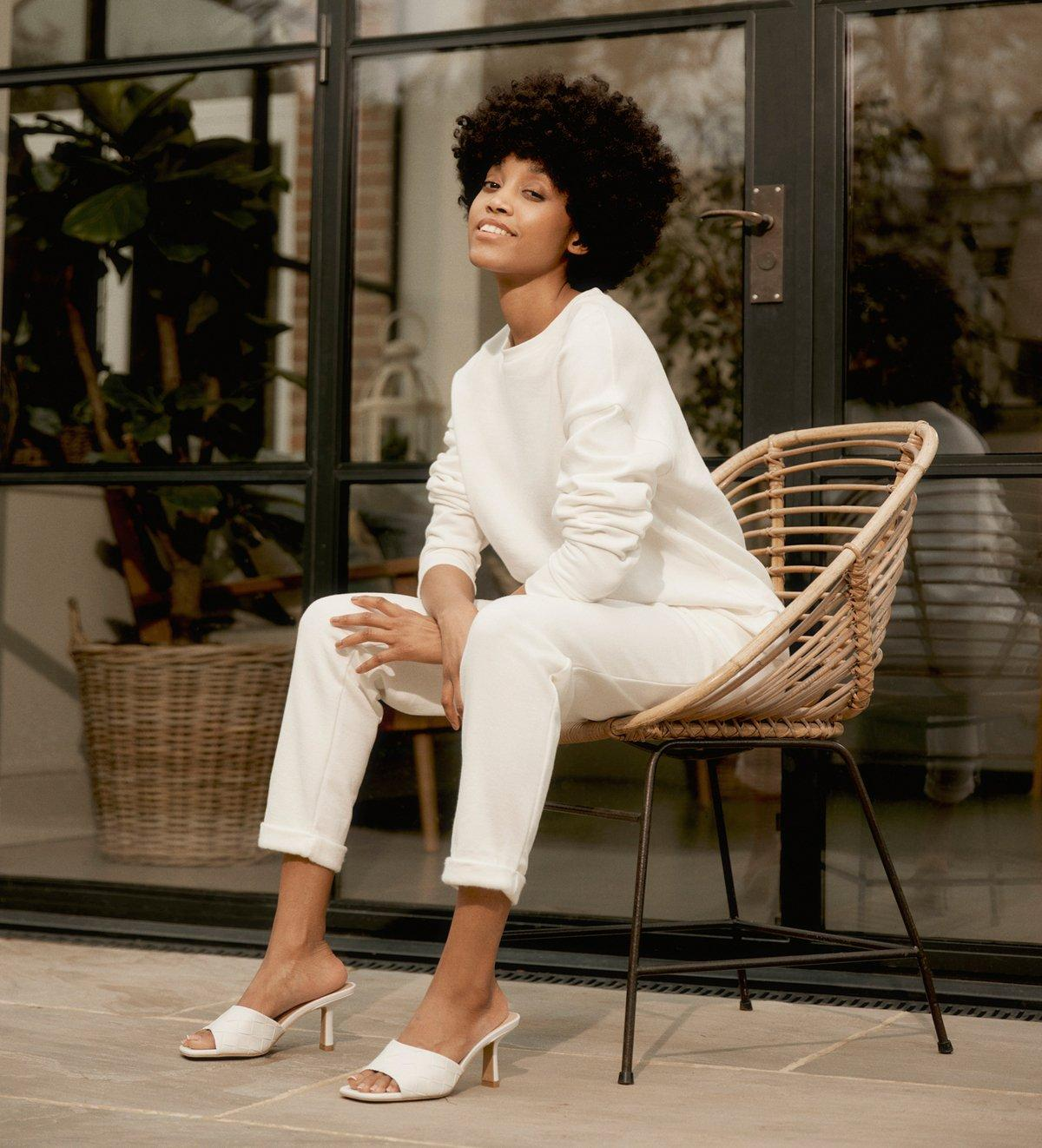 Model sits on chair wearing white top, trousers and shoes.